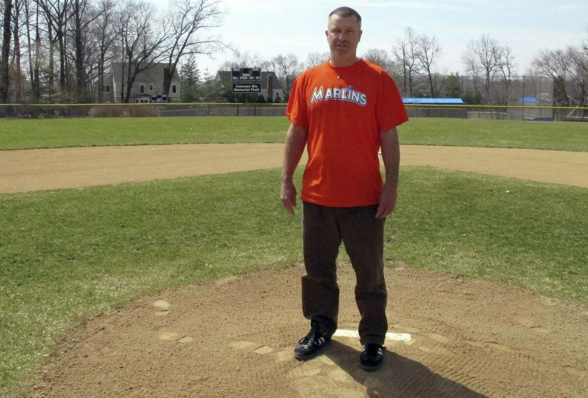 In this April 6, 2015 photo, Christopher Stefanoni poses at the Darien Little League park in Darien, Conn. Stefanoni is suing the Darien Little League in federal court, saying league officials demoted his 9-year-old son to a lower-level team as retribution for his affordable housing proposal. Lawyers for the Little League deny the allegations.