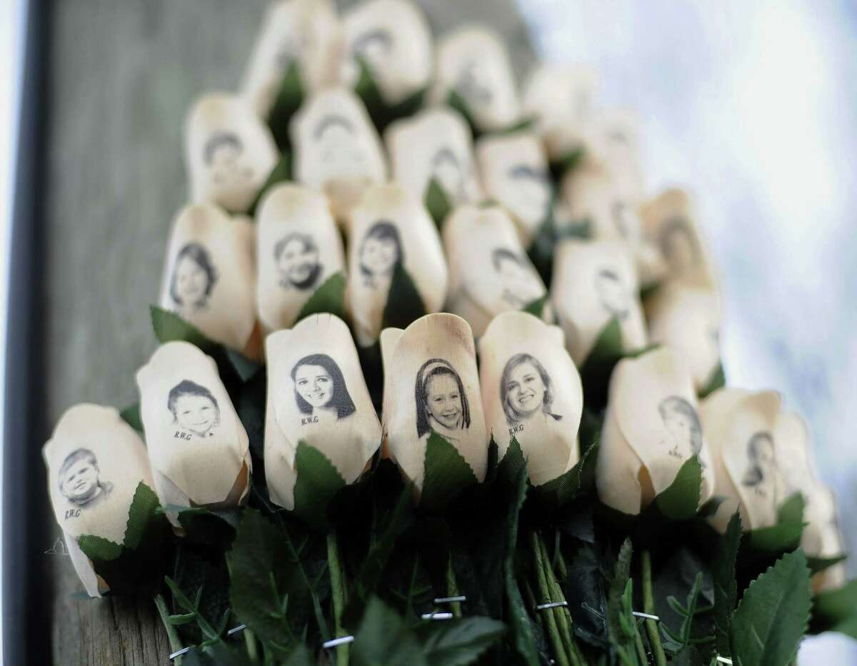 In this Jan. 14, 2013 photo, white roses with the faces of victims of the Sandy Hook Elementary School shooting are attached to a telephone pole near the school on the one-month anniversary of the shooting that left 26 dead in Newtown, Conn.