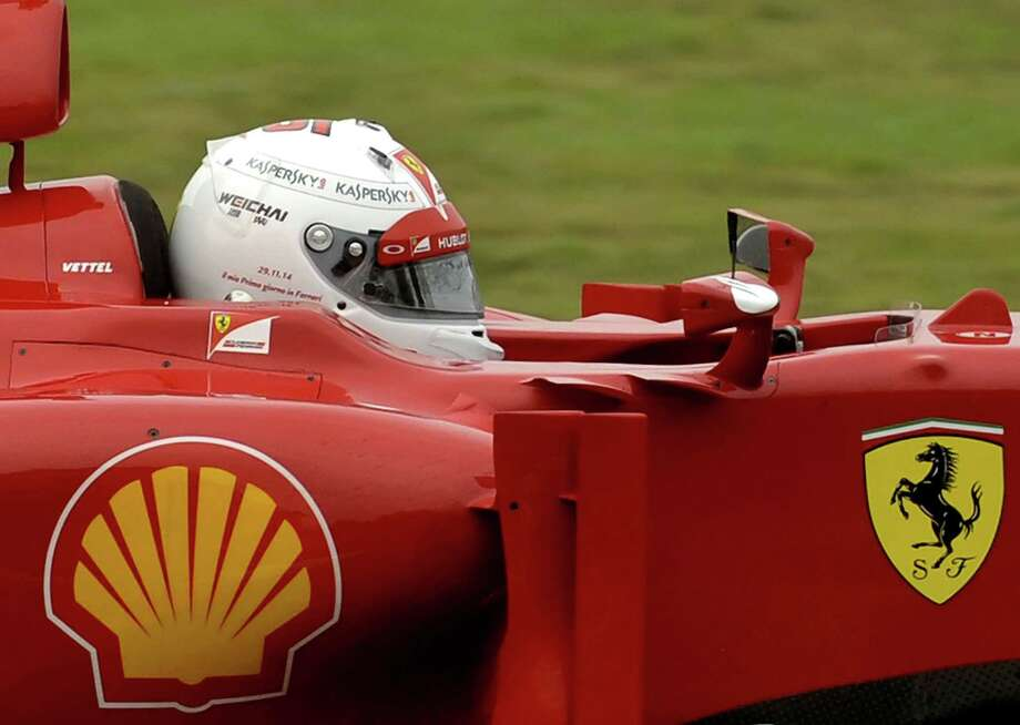 """FILE -- In this Nov. 29, 2014 file photo, Sebastian Vettel wears a white helmet with the words, """"My first day at Ferrari"""" plus the date, written on it, as he steers an F2012 car from two seasons ago, at Ferrari's private Fiorano circuit. Ferrariís sleek sports cars and souped-up Formula 1 racing machines have made the prancing horse logo among the worldís most powerful brands. Now, as the company prepares for a public listing, it wants to cash in on the cachet. (AP Photo/Marco Vasini) Photo: AP / AP"""