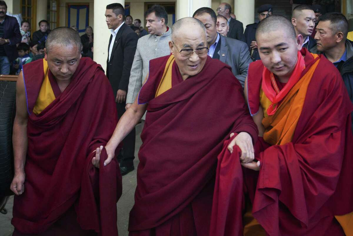 Tibetan spiritual leader the Dalai Lama, center, is helped by attendant monks as he leaves after his religious talk at the Tsuglakhang temple in Dharmsala, India, Friday, Dec. 5, 2014. The four-day talk for a Mongolian Buddhist group ended Friday. (AP Photo/Ashwini Bhatia)