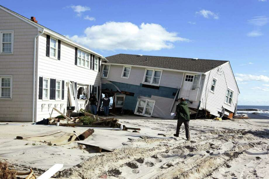 People survey damage to beachfront houses on New Jerseyís Long Beach Island in the wake of Superstorm Sandy. Federal flood insurance rates climbed 18 percent for those living in flood prone areas like those affected by Sandy. Photo: AP Photo/Philadelphia Inquirer, Ed Hille  / The Philadelphia Inquirer