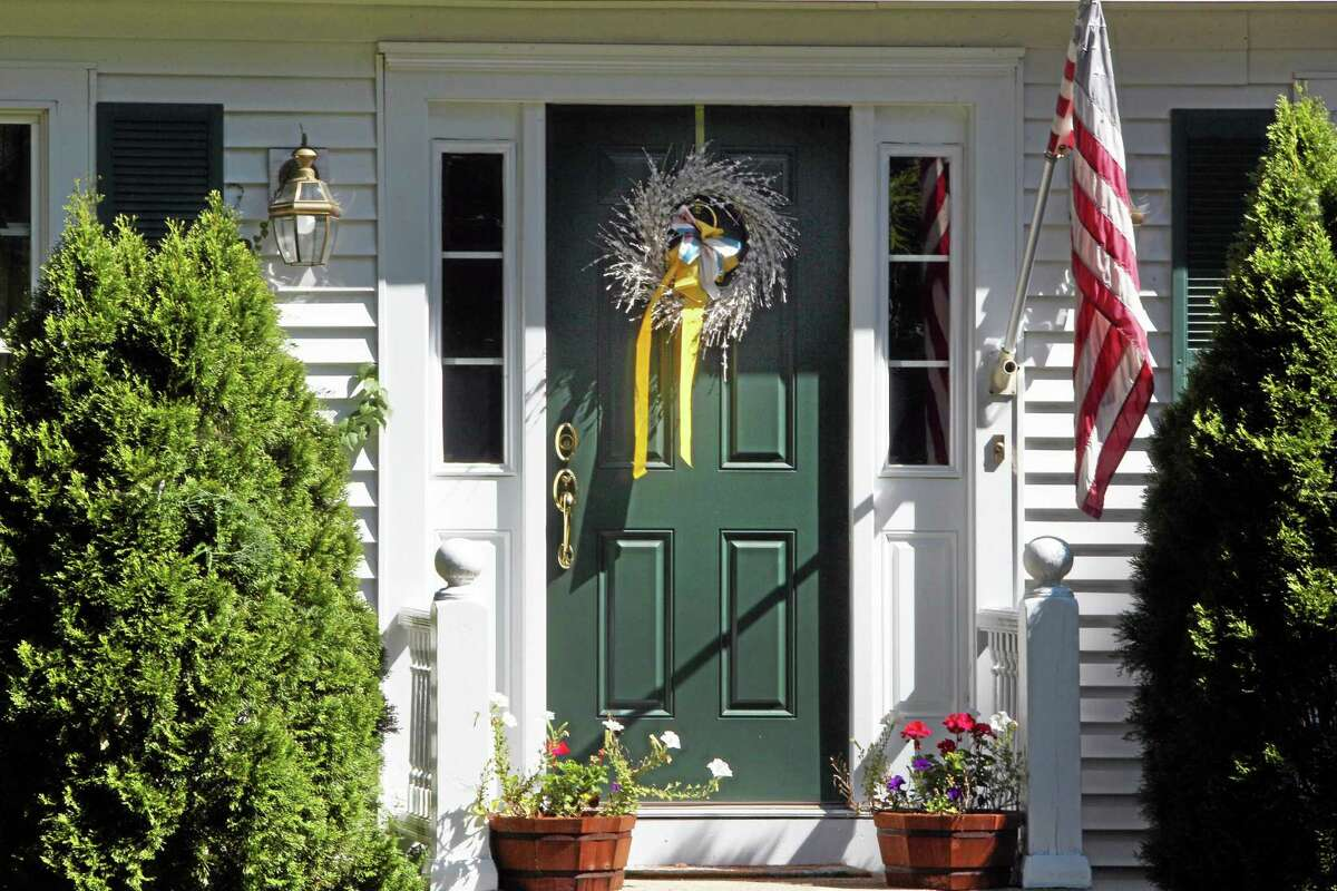 A ribbon is seen on the front door of the family home of freelance journalist James Foley, Wednesday, Aug. 20, 2014 in Rochester, N.H. Foley was abducted in November 2012 while covering the Syrian conflict. On Tuesday, Aug. 19, militants with the Islamic State extremist group released a video showing Islamic State militants beheading Foley in an act of revenge for U.S. airstrikes in northern Iraq . (AP Photo/Jim Cole)