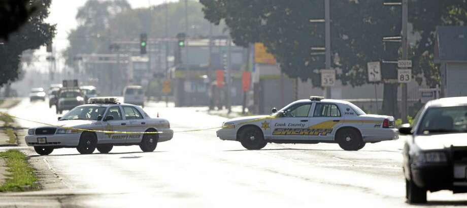 Police cars block an intersection as law enforcement officials continue to negotiate with at least one hostage-taker for the release of two children and two adults he is still holding inside a house in the southern Chicago suburb of Harvey, Wednesday, Aug. 20, 2014. The standoff began at 12:45 p.m. Tuesday when Harvey police responded to reports from a neighbor of a possible burglary at the home. Two officers were wounded in an initial exchange of gunfire. (AP Photo/M. Spencer Green) Photo: AP / AP