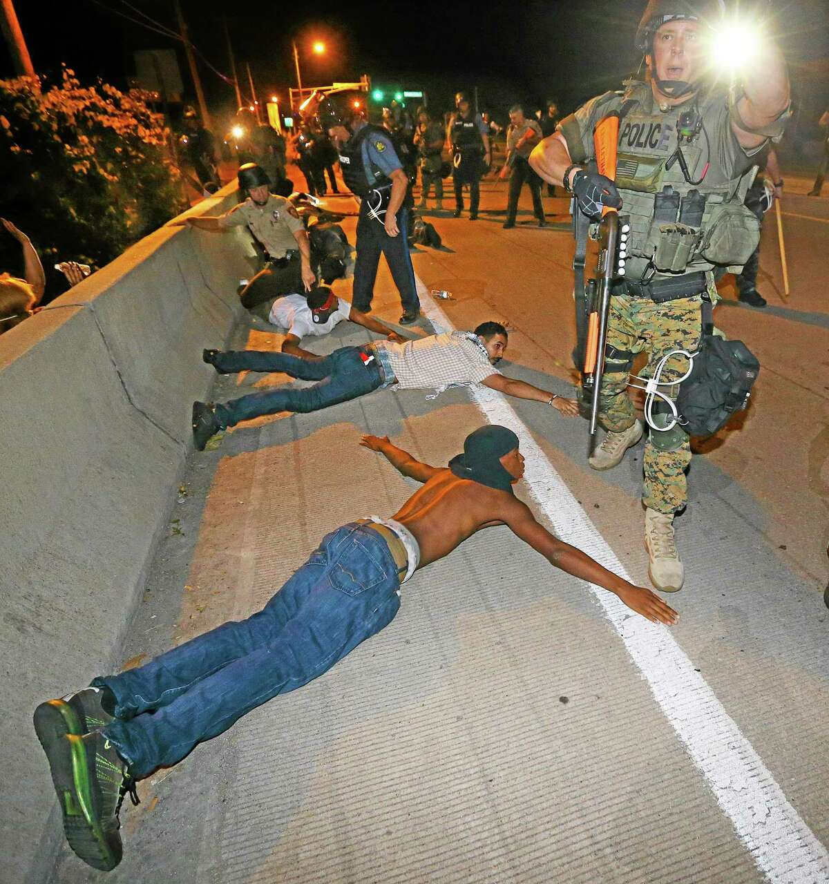 Police begin arresting dozens of protesters on West Florissant Avenue after they refused to leave the area and some began throwing objects at officers in Ferguson, Mo. early Wednesday, Aug. 20, 2014. On Aug. 9, 2014, a white police officer fatally shot Michael Brown, an unarmed black 18-year old, in the St. Louis suburb. (AP Photo/Atlanta Journal-Constitution, Curtis Compton)