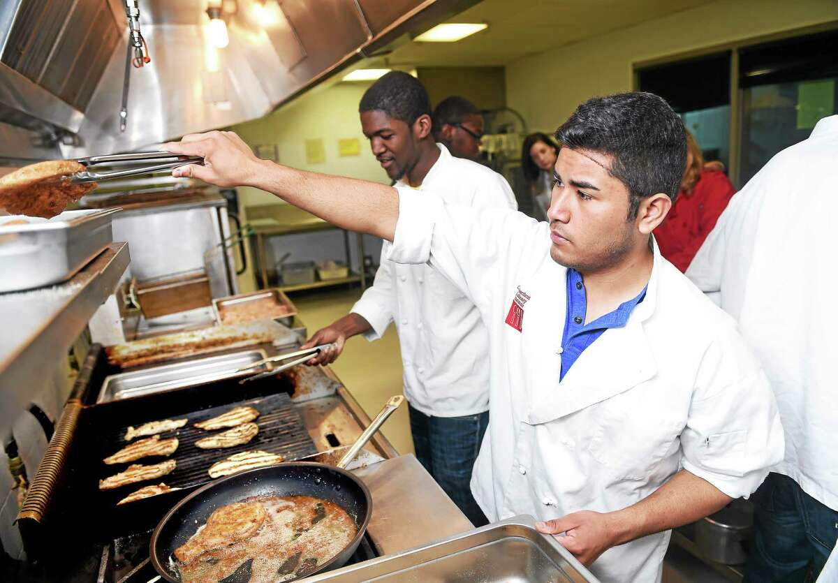 Senior Abdiel Cambos (right), 18, fries pork chops for the next day's teachers lunch at Wilbur Cross High School in New Haven on 4/8/2015.