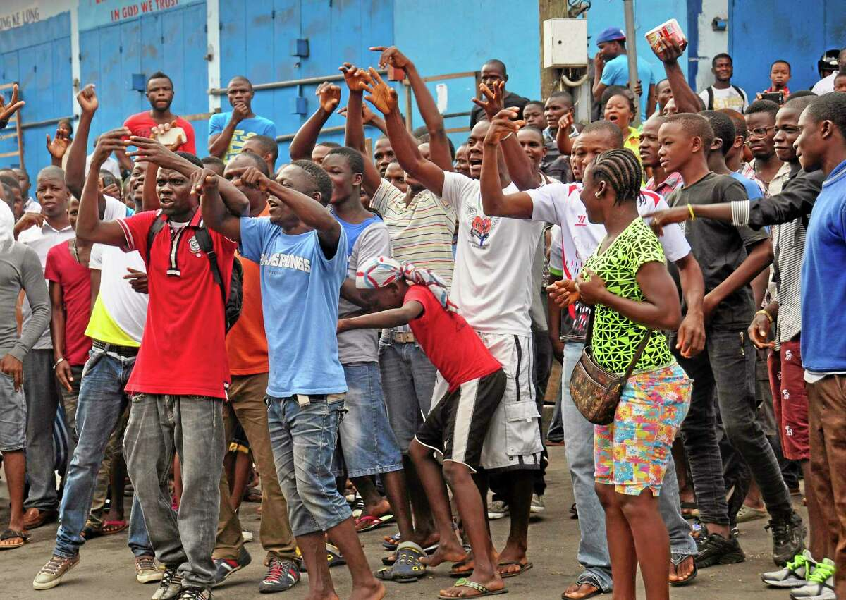 Residents from an area close to the West Point Ebola center, protest as they are not allowed to enter the area leading to their homes, after Liberia security forces blocked roads, as the government clamps down on the movement of people to prevent the spread of the Ebola virus in the city of Monrovia, Liberia, Wednesday, Aug. 20, 2014. Security forces deployed Wednesday to enforce a quarantine around a slum in the Liberian capital, stepping up the governmentís fight to stop the spread of Ebola and unnerving residents.(AP Photo/Abbas Dulleh)
