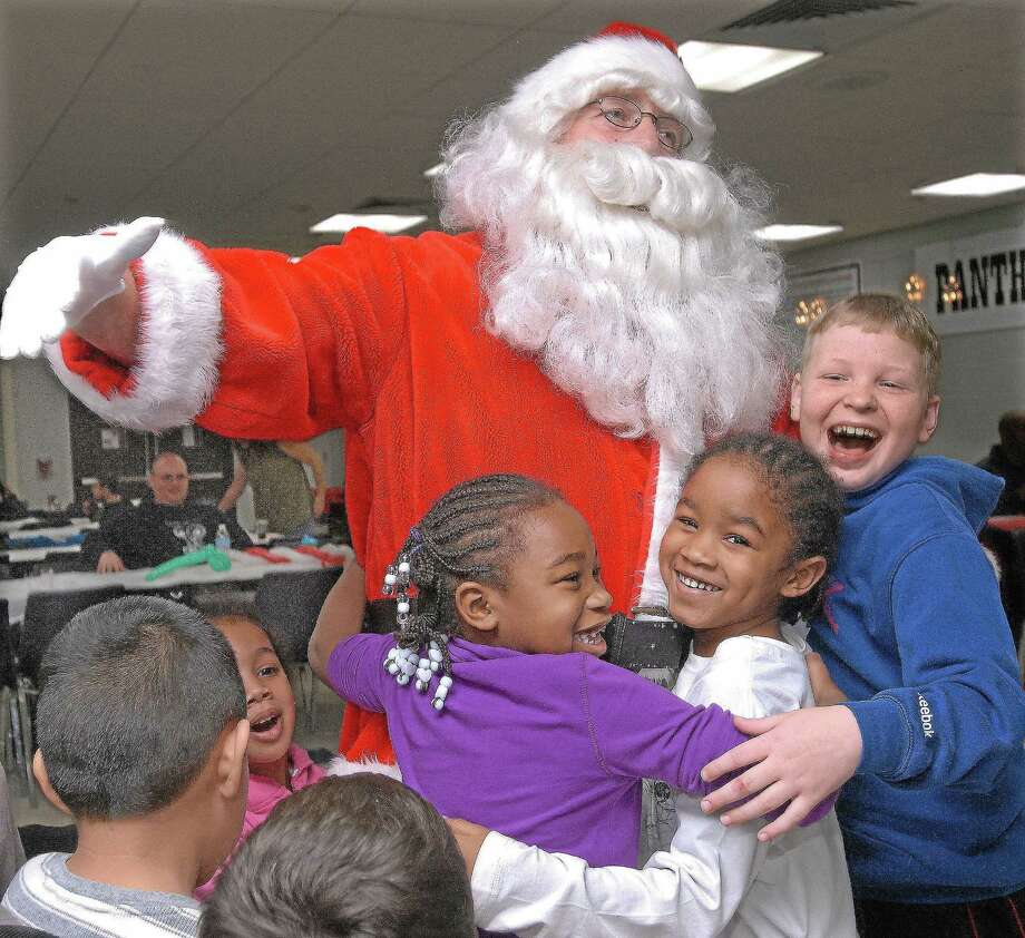 In this file photo, Cromwell residents Talia Jones, 6, her twin brother Tarrell Jones and Brandon Stefurak, 11, greet Santa on his arrival at the annual Santa's Workshop last year. Photo: File Photo