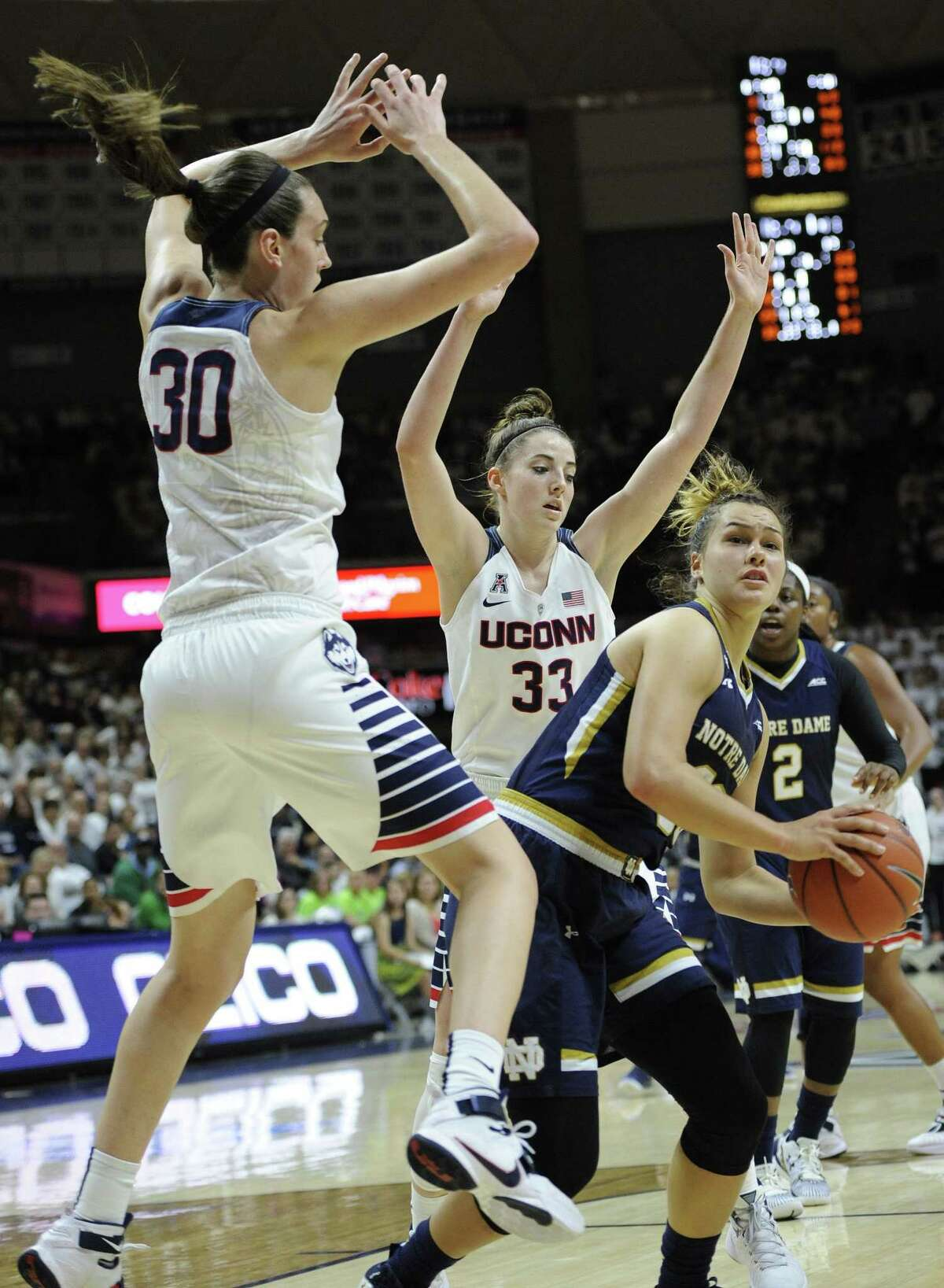 UConn's Breanna Stewart, left, and Katie Lou Samuelson, center, guard Notre Dame's Kathryn Westbeld during Saturday's game.