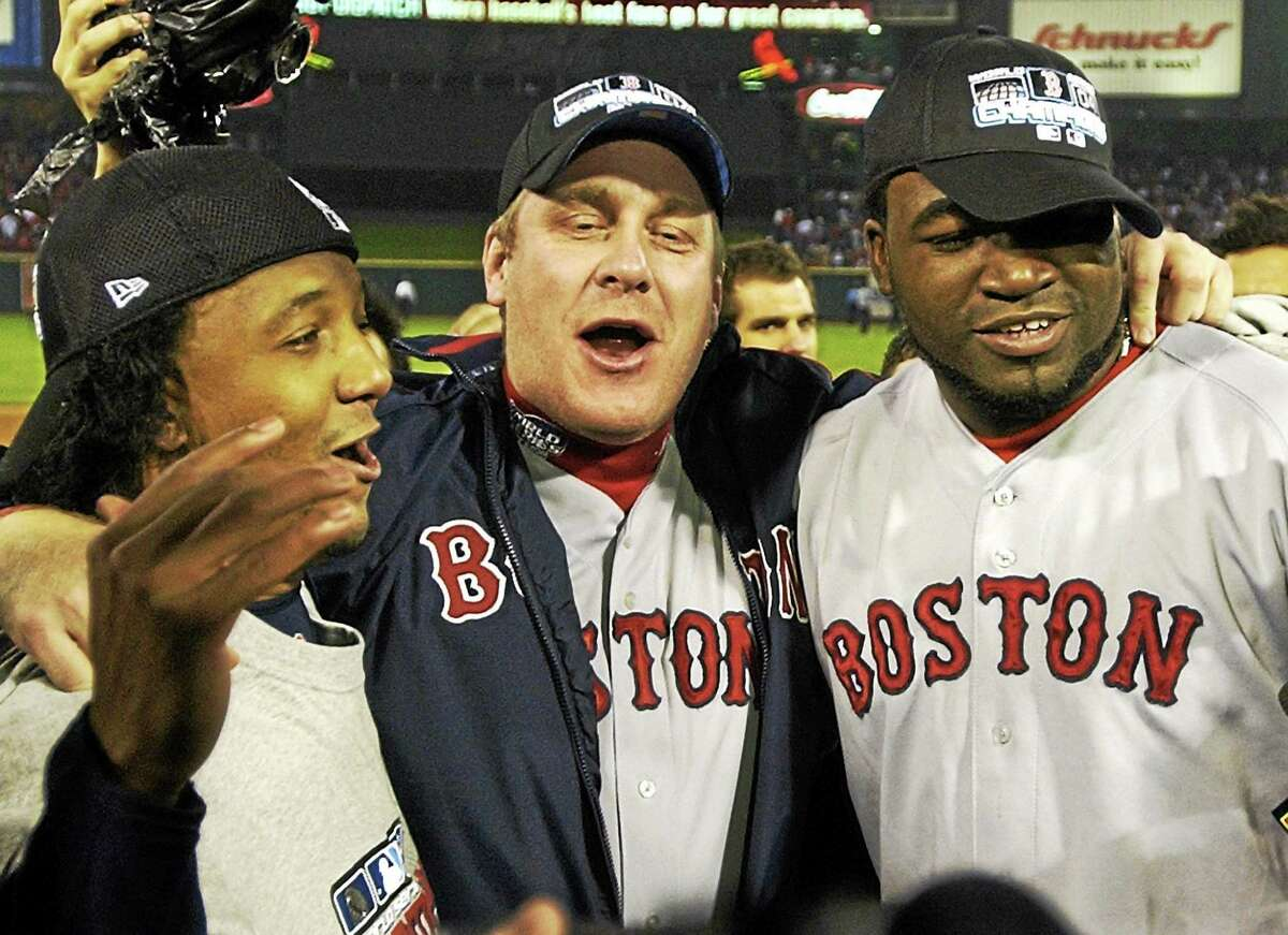 Boston Red Sox players, from left, Pedro Martinez, Curt Schilling and David Ortiz celebrate after defeating the St. Louis Cardinals 3-0 in Game 4 to win the World Series at Busch Stadium in St. Louis on Oct. 27, 2004.