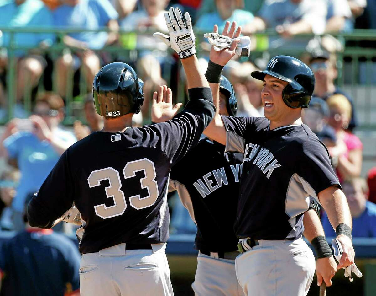 New York Yankees' Kelly Johnson (33) and Mark Teixeira (25) celebrate Johnson's two-run home run in the third inning of a exhibition baseball game against the Houston Astros, Saturday, March 8, 2014, in Kissimmee, Fla. (AP Photo/Alex Brandon)