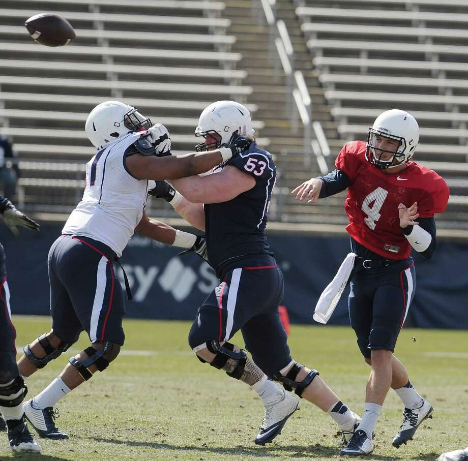 UConn quarterback Bryant Shirreffs throws over White's Omaine Stephens, left, and Blue's Andres Knappe during the first half of the annual Blue-White spring game on Saturday at Rentschler Field. Photo: Jessica Hill — The Associated Press  / FR125654 AP