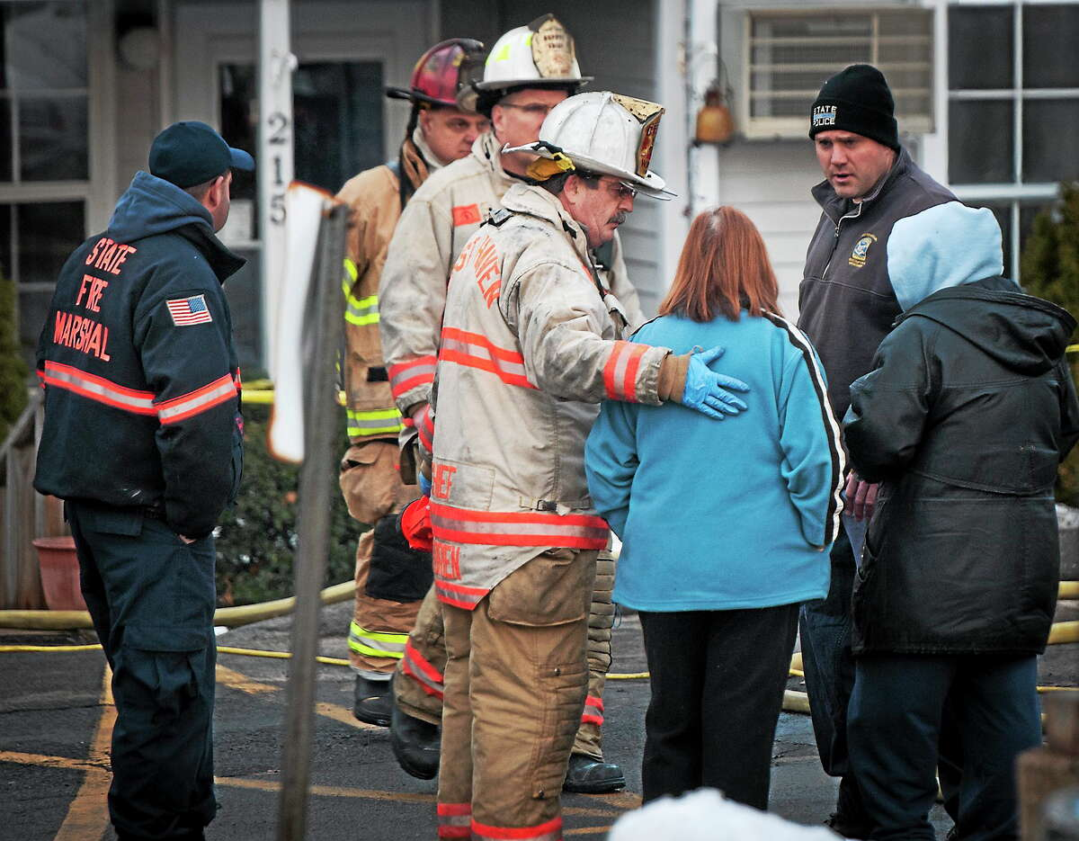 Fire Chief James O'Brien talks with a woman at the scene of a triple-fatal fire in West Haven on Tuesday.