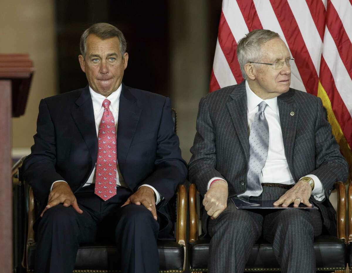 In this Sept. 10, 2014 photo, Speaker of the House John Boehner, R-Ohio, left, and Senate Majority Leader Harry Reid, D-Nev., right, attend a ceremony remembering the attacks of September 11, 2001, at the Capitol in Washington.