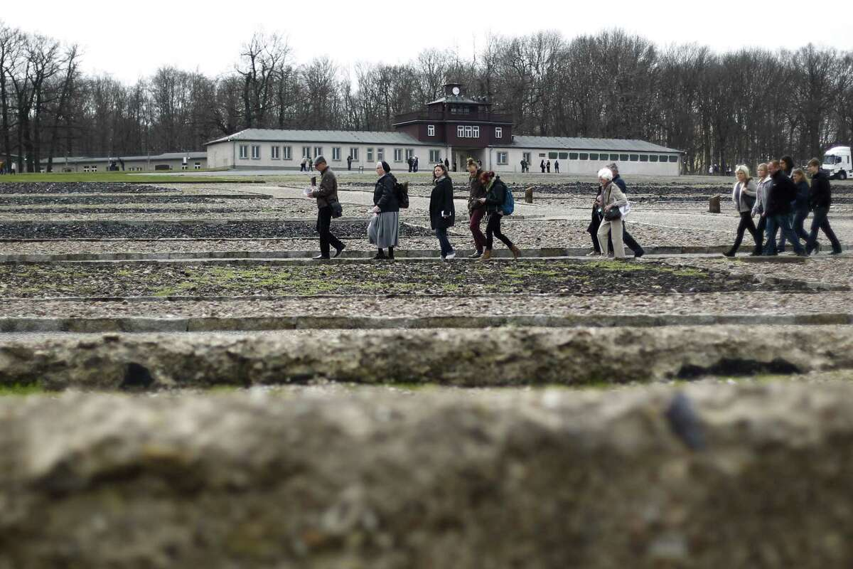 Visitors walk through the former concentration camp Buchenwald on the 70th anniversary of the liberation of the former Nazi concentration camp Buchenwald near Weimar, Germany Saturday, April 11, 2015. On April 11, 1945 the Buchenwald concentration camp was liberated by the United States Army. (AP Photo/Markus Schreiber)