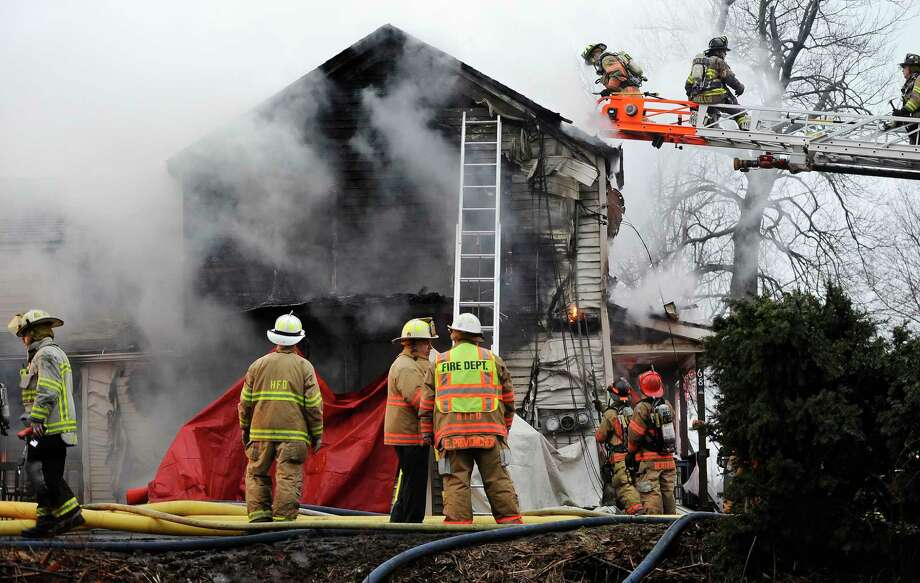 Firefighters control a house fire where four people were reportedly unaccounted for, Wednesday, Dec. 10, 2014, in Enfield, Conn., about 20 miles northeast of Hartford. Photo: (AP Photo/Journal Inquirer, Jessica Hill)  / Journal Inquirer