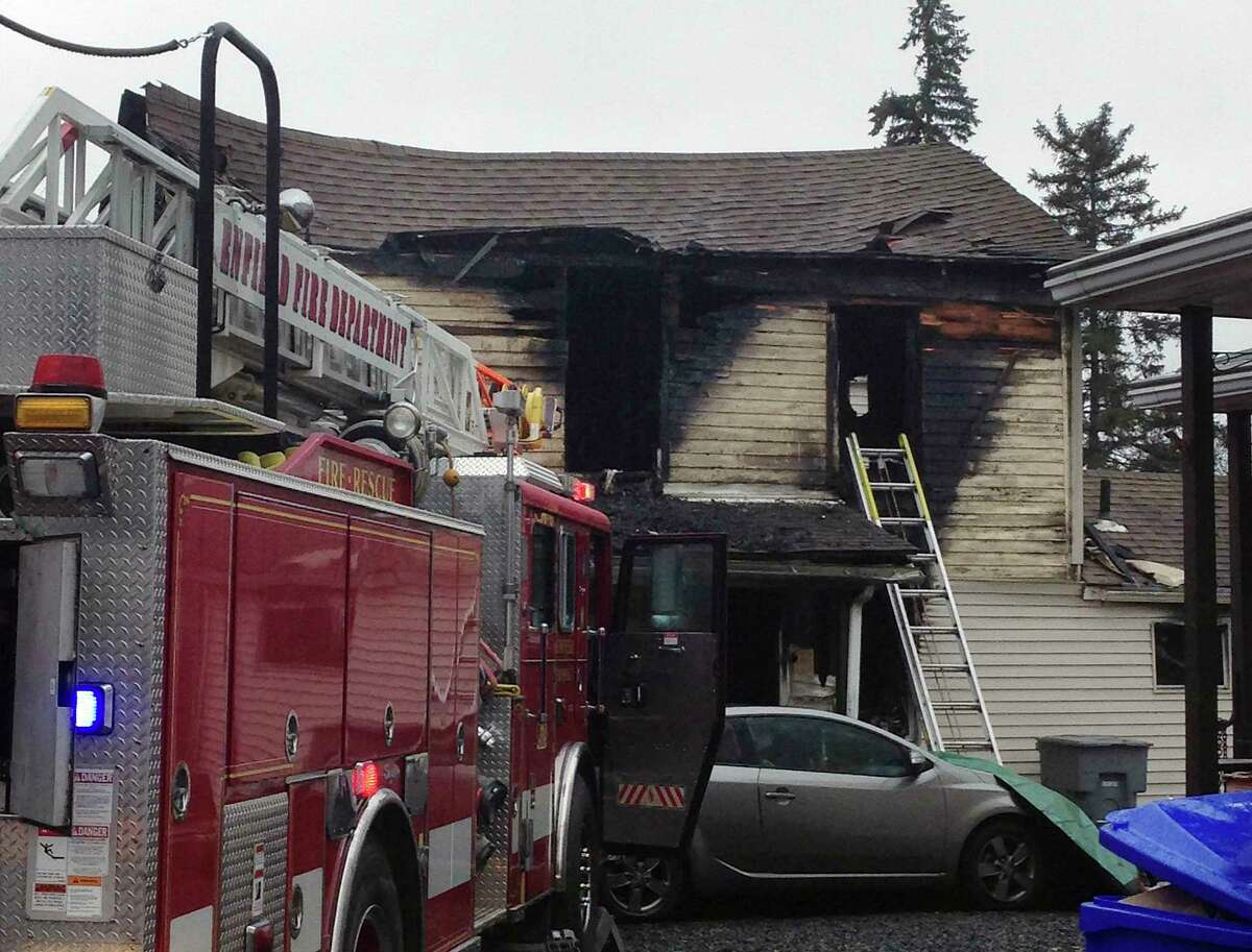 A fire truck sits at the scene of a fire Wednesday morning, Dec. 10, 2014, at a two-family home in Enfield, Conn. Officials said at least four people were unaccounted for.