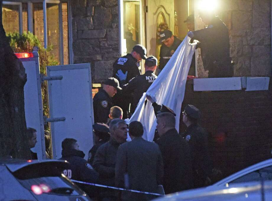 Police Department personnel remove one of the bodies from a home where four people were found dead Friday, April 10, 2015, in the Floral Park neighborhood in New York, next to Long Island's Nassau County. Police say the four people in their 70s and 80s have been found dead in an apparent carbon monoxide poisoning after a car was left running in an attached garage. (AP Photo/Louis Lanzano) Photo: AP / FR77522 AP