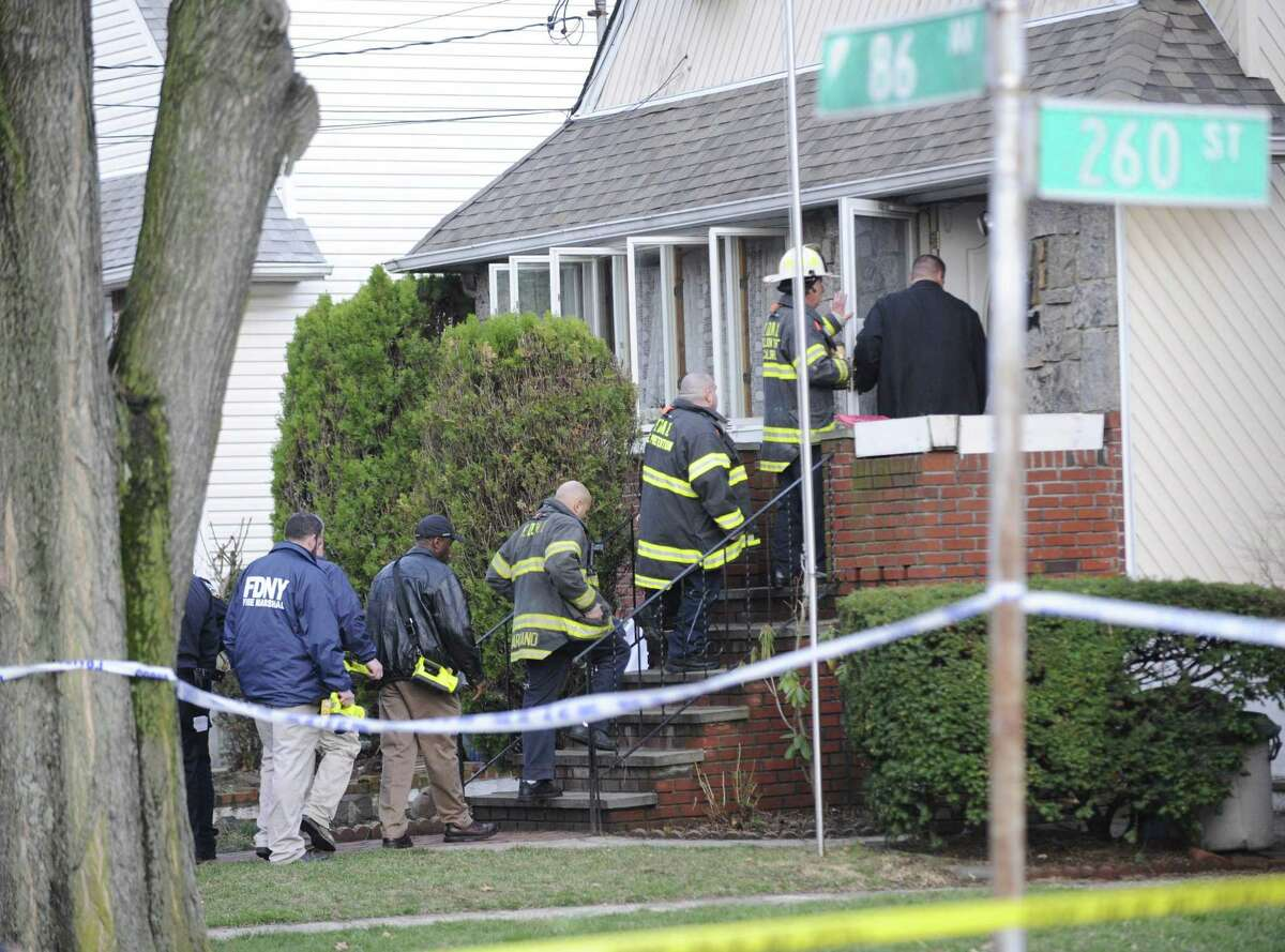 Officials gather at a home where four people were found dead Friday, April 10, 2015, in the Floral Park neighborhood in New York, next to Long Island's Nassau County. Police say the four people in their 70s and 80s have been found dead in an apparent carbon monoxide poisoning after a car was left running in an attached garage. (AP Photo/Louis Lanzano)