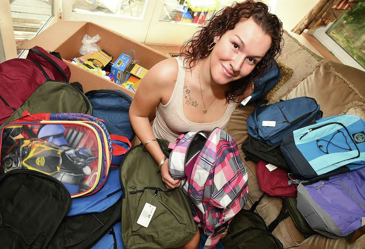 Mariah Moore, 22, in the living room of her family's home in Cromwell, fills 150 backpacks with school supplies that she will donate to students of need at Macdonough Elementary School in Middletown. Moore, a certified nurses aid at Middlesex Hospital, is a student at Middlesex Community College and has aspirations to be a nurse or an occupational therapist.
