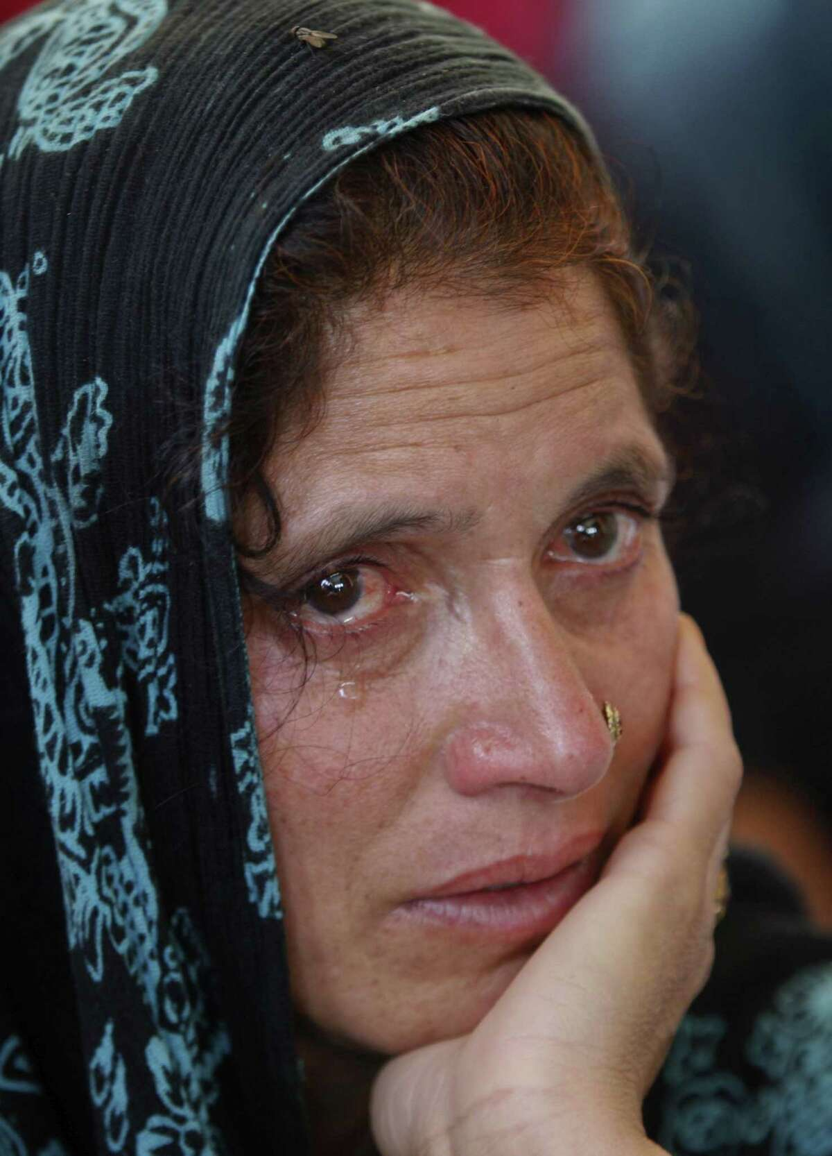 A relative weeps during the funeral of Indian civilian Sarpanch Karamat Hussain who was killed in Pakistani shelling at Balakot sector in Poonch, Jammu and Kashmir, India on Aug.16, 2015.