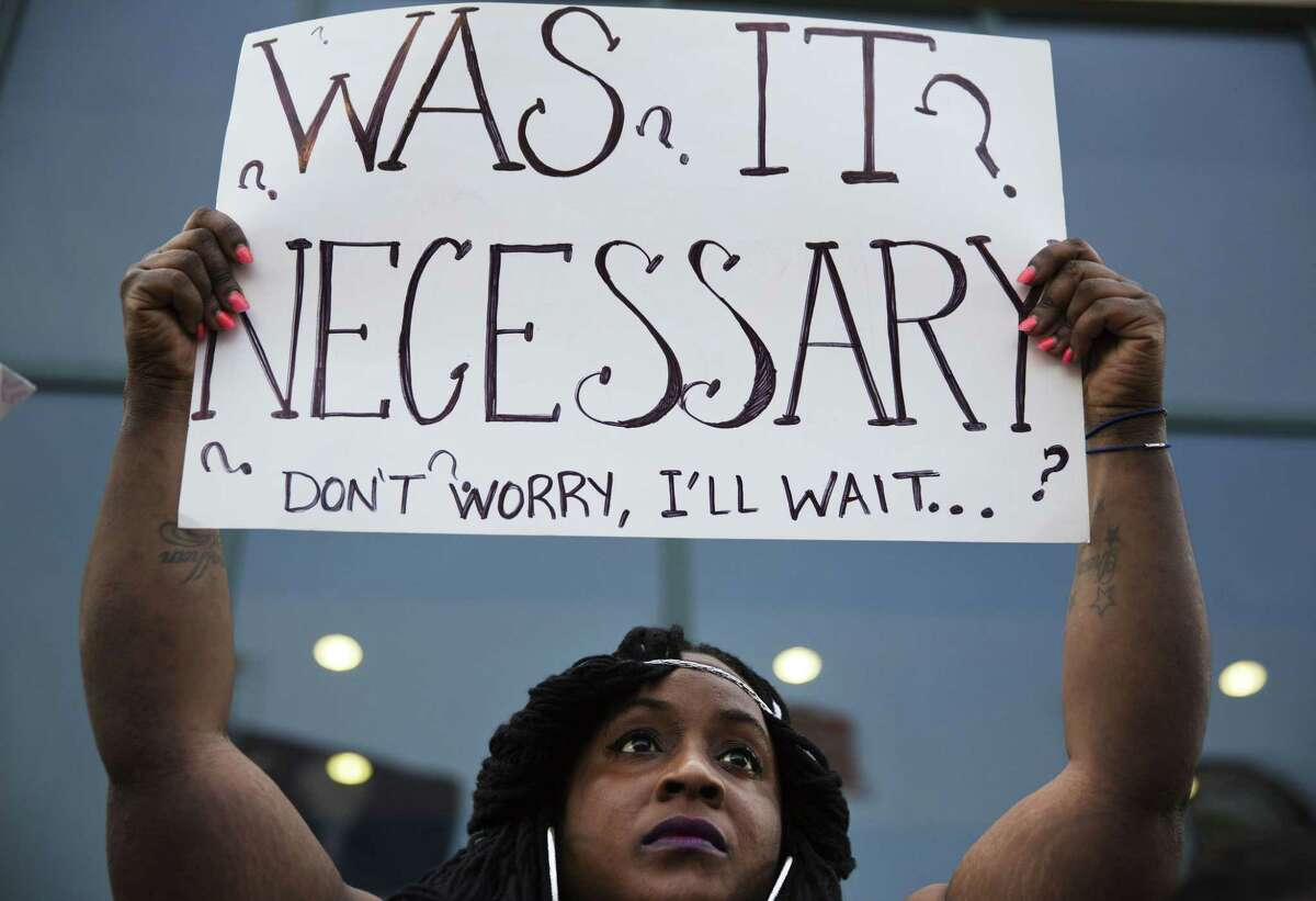 Laquanda Multrie, of Charleston, S.C., holds a sign during a rally in North Charleston, S.C. on Friday, April 10, 2015 protesting the fatal police shooting of Walter Scott. Scott was killed by a police officer after a traffic stop on Saturday. Officer Michael Slager has been fired and charged with murder. (AP Photo/David Goldman)
