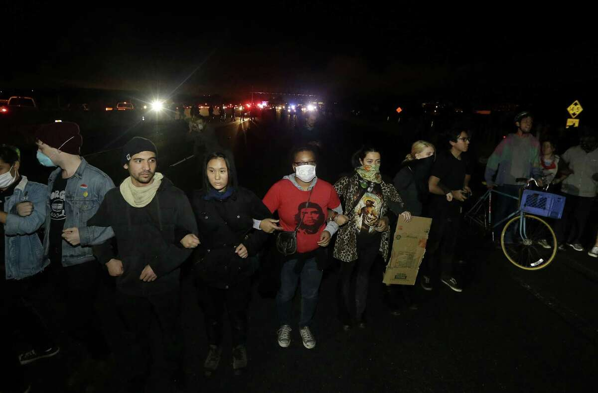 FILE- In this Dec. 8, 2014, file photo, protesters lock arms as they block traffic on Highway 80 in Berkeley, Calif., in response to police killings in Missouri and New York. Across the country, protesters angered at the killing of unarmed black men by white police officers have turned out in recent days in cities and towns. They are college students and grandmothers, experienced protesters as well as novices, often as many white as black. (AP Photo/Jeff Chiu, File)