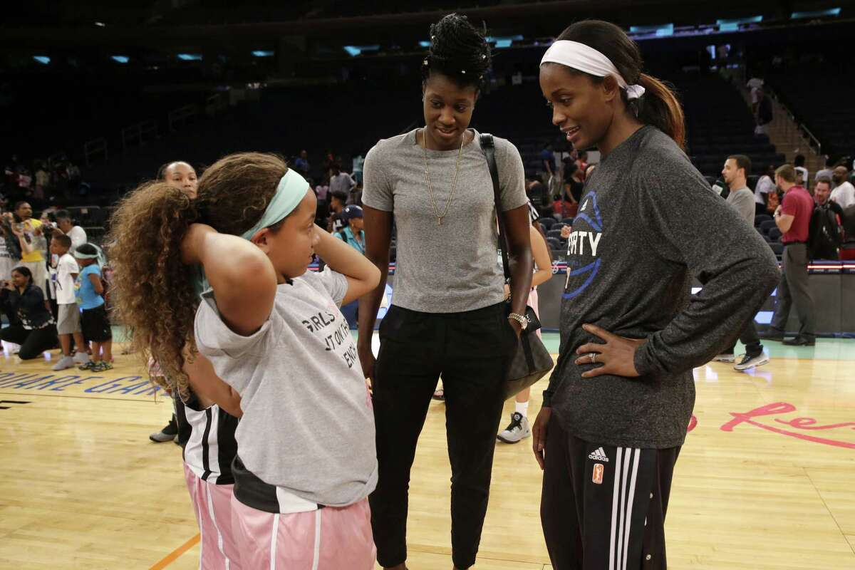 Kymora Johnson, left, of the Charlottesville Cavaliers, talks to New York Liberty center Tina Charles, center, and forward Swin Cash Saturday at Madison Square Garden.