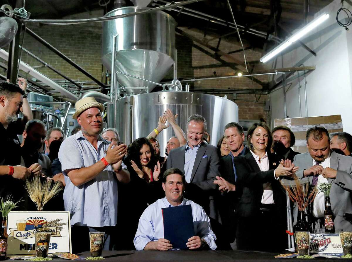 Supporters clap after Arizona Gov. Doug Ducey, center, signed Senate Bill 1030 at Four Peaks Brewery in Tempe, Ariz.