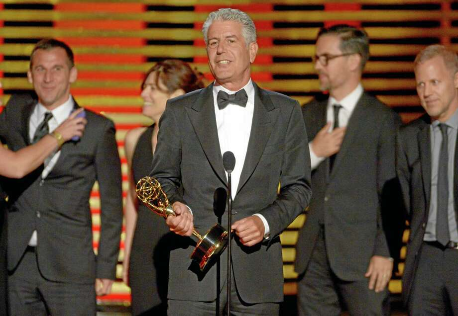 """Anthony Bourdain and the team of """"Anthony Bourdain: Parts Unknown"""" accept the award for outstanding informational series or special at the Television Academy's Creative Arts Emmy Awards at the Nokia Theater L.A. LIVE on Saturday, Aug. 16, 2014, in Los Angeles. Photo: Phil McCarten — Invision For The Television Academy — AP Images / Invision"""
