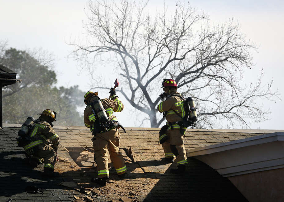 Conroe firefighters carve a hole in the roof to vent smoke and heat on Monday, Jan. 2, 2017, after a fire broke out at the Saltgrass Steak House off of Interstate 45 North in Conroe. Photo: Michael Minasi, Staff / © 2017 Houston Chronicle