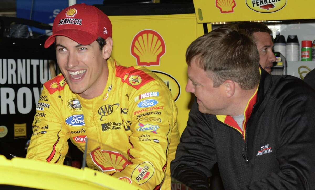 NASCAR driver Joey Logano, left, laughs while chatting with his crew in the garage during a practice session for the Texas Motor Speedway on Friday in Fort Worth, Texas.