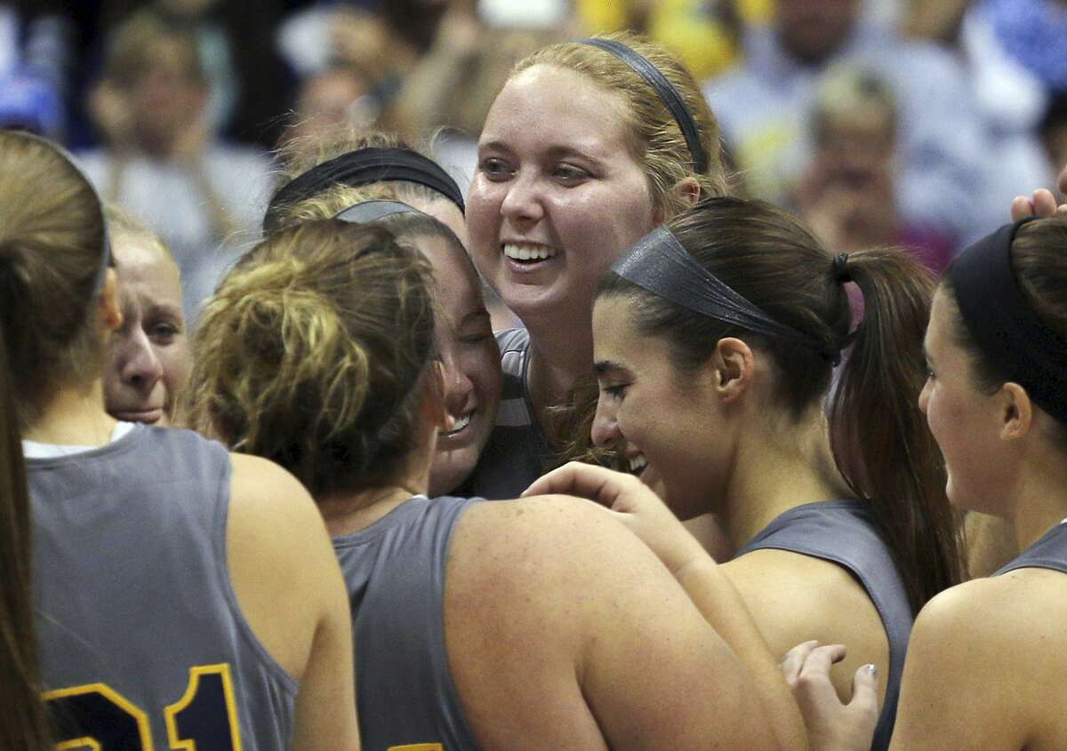 In this Nov. 2, 2014 file photo, Mount St. Joseph's Lauren Hill gets congratulated by teammates after scoring during her first NCAA basketball game against Hiram University in Cincinnati. The 19-year-old freshman died at a hospital Friday.