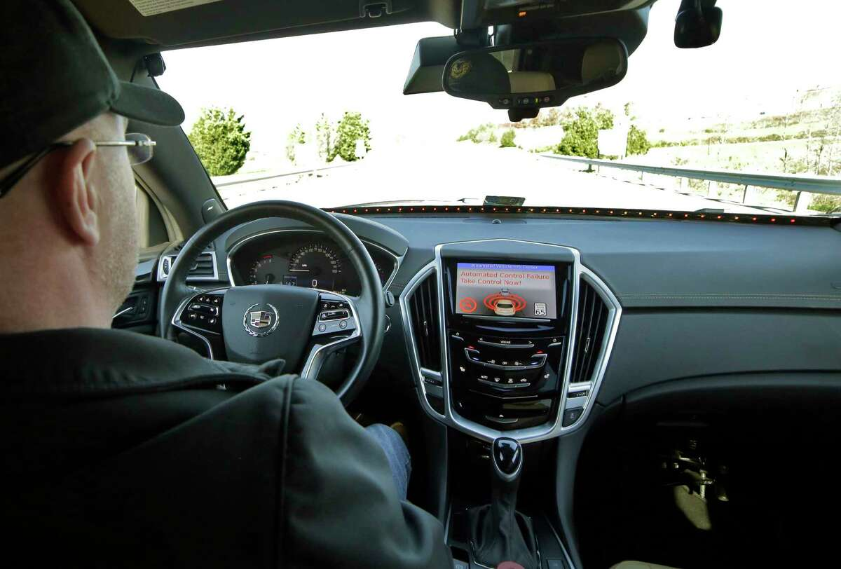 Virginia Tech Center for Technology Development Program Administration Specialist Greg Brown behind the wheel of a driverless car during a test ride showing the alert system handing over automation to the driver while traveling street in Blacksburg, Va.