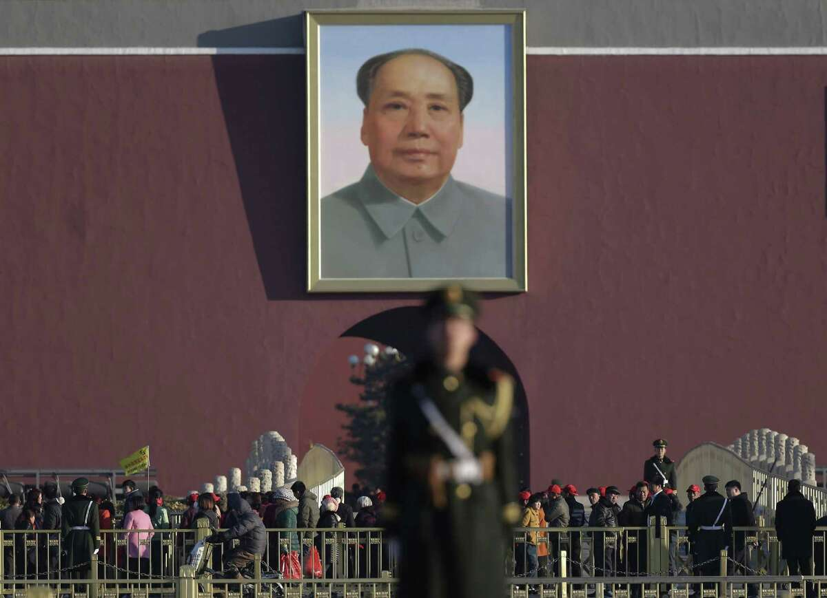 "FILE - In this March 10, 2015 file photo, Chinese paramilitary policemen stand watch visitors near a portrait of Mao Zedong after they sealed off Tiananmen Square for the public during a plenary session of the Chinese People's Political Consultative Conference at the Great Hall of the People in Beijing. China's state broadcaster is investigating one of its hosts after a video of him insulting Mao Zedong was leaked, causing a stir and rekindling debate on the complicated legacy of the father of communist China. China Central Television said Wednesday, April 8, talent show host Bi Fujian would face serious investigation because his jokes have had a ""severe social impact."""