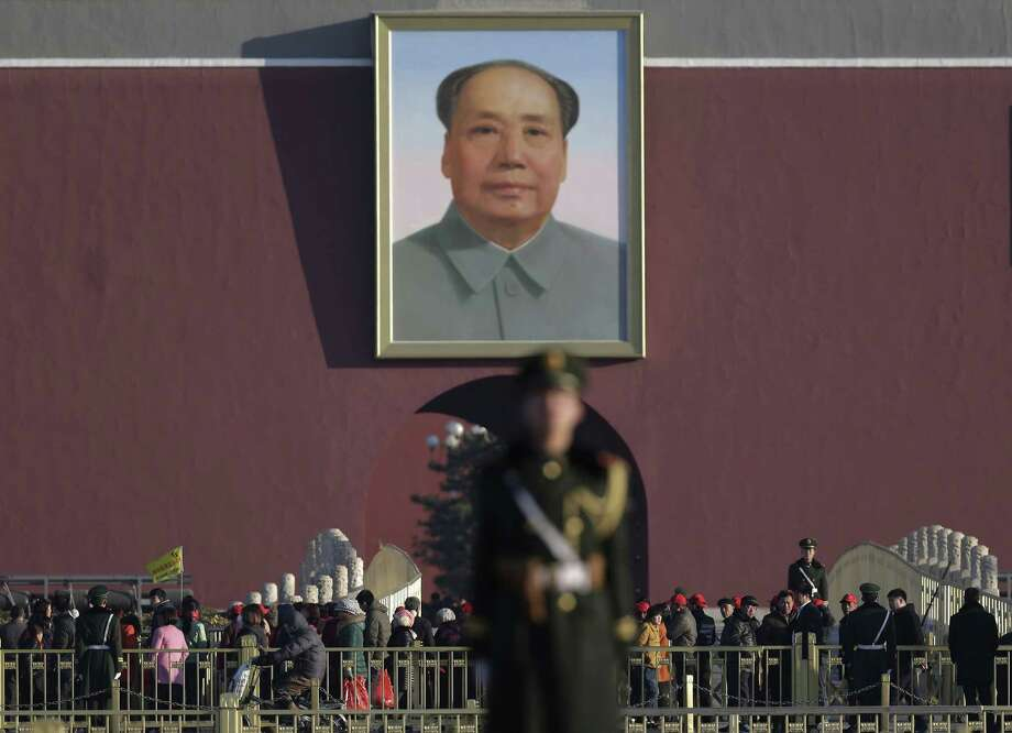 """FILE - In this March 10, 2015 file photo, Chinese paramilitary policemen stand watch visitors near a portrait of Mao Zedong after they sealed off Tiananmen Square for the public during a plenary session of the Chinese People's Political Consultative Conference at the Great Hall of the People in Beijing. China's state broadcaster is investigating one of its hosts after a video of him insulting Mao Zedong was leaked, causing a stir and rekindling debate on the complicated legacy of the father of communist China. China Central Television said Wednesday, April 8, talent show host Bi Fujian would face serious investigation because his jokes have had a """"severe social impact."""" Photo: (AP Photo/Andy Wong, File) / AP"""