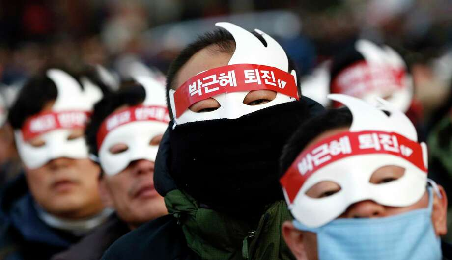 South Korean protesters attend an anti-government rally in downtown Seoul, South Korea, Saturday, Dec. 5, 2015. Wearing white half-masks and carrying flowers and banners, thousands of South Koreans marched in Seoul on Saturday against conservative President Park Geun-hye, who had compared masked protesters to terrorists after clashes with police broke out at a rally last month. Photo: AP Photo/Lee Jin-man / AP