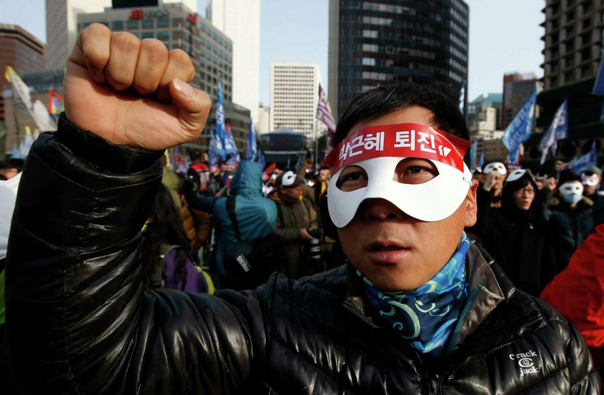 South Korean protesters attend an anti-government rally in downtown Seoul, South Korea, Saturday, Dec. 5, 2015. Wearing white half-masks and carrying flowers and banners, thousands of South Koreans marched in Seoul on Saturday against conservative President Park Geun-hye, who had compared masked protesters to terrorists after clashes with police broke out at a rally last month.