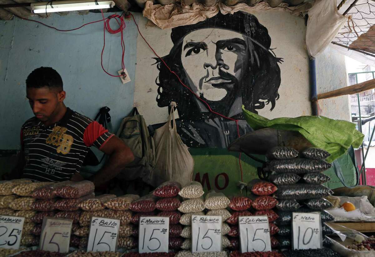 """A man works at a bean stall at a market beside a mural with the a picture of revolution hero Ernesto """"Che"""" Guevara in Havana, Cuba, Thursday, April 9, 2015. President Barack Obama signaled Thursday he will soon remove Cuba from the U.S. list of state sponsors of terrorism, boosting hopes for improved ties as he prepared for a historic encounter with Cuban President Raul Castro during the Summit of the Americas taking place in Panama."""