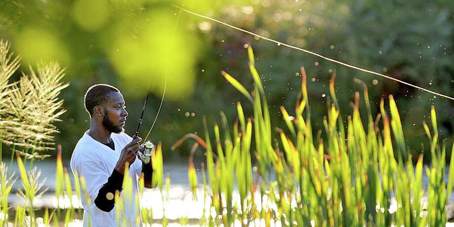 """Derrick White, a resident of South Carolina hoping to pull in a blue gill, bass or catfish but admits he will take """"whatever will bite"""" while fishing Tuesday evening at Butternut Hollow in Middletown. White is visiting family in Middletown this week. Photo: Journal Register Co. / TheMiddletownPress"""