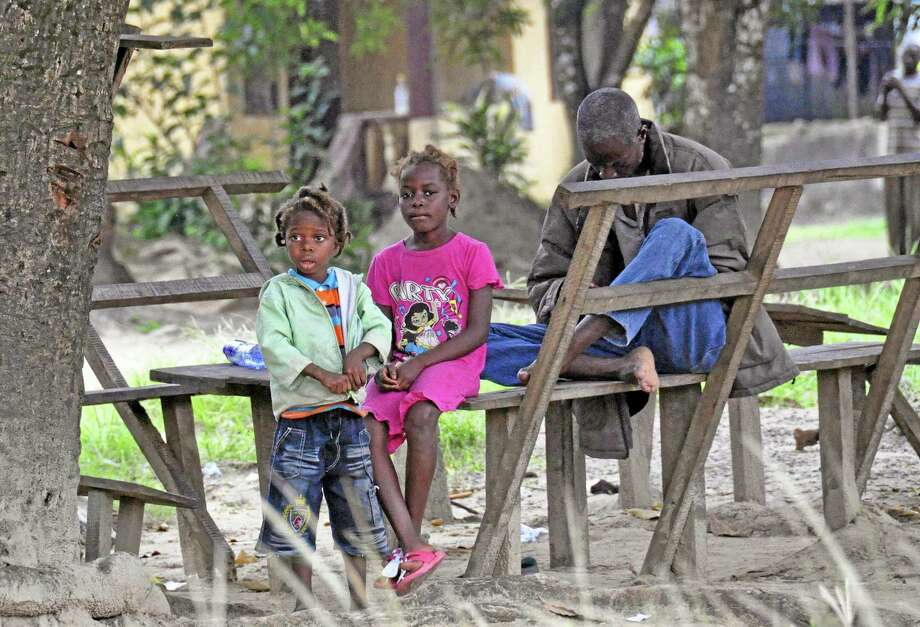 In this photo taken on Saturday, Aug. 16, 2014, a family sit near the body of their mother suspected of dying from the Ebola virus, as the father, right, tries to contact family members on his mobile phone, in Monrovia, Liberia. Liberian officials fear Ebola could soon spread through the capital's largest slum after residents raided a quarantine center for suspected patients and took items including blood-stained sheets and mattresses. The violence in the West Point slum occurred late Saturday and was led by residents angry that patients were brought from other parts of the capital to the holding center, Tolbert Nyenswah, assistant health minister, said Sunday. (AP Photo/Abbas Dulleh) Photo: AP / AP