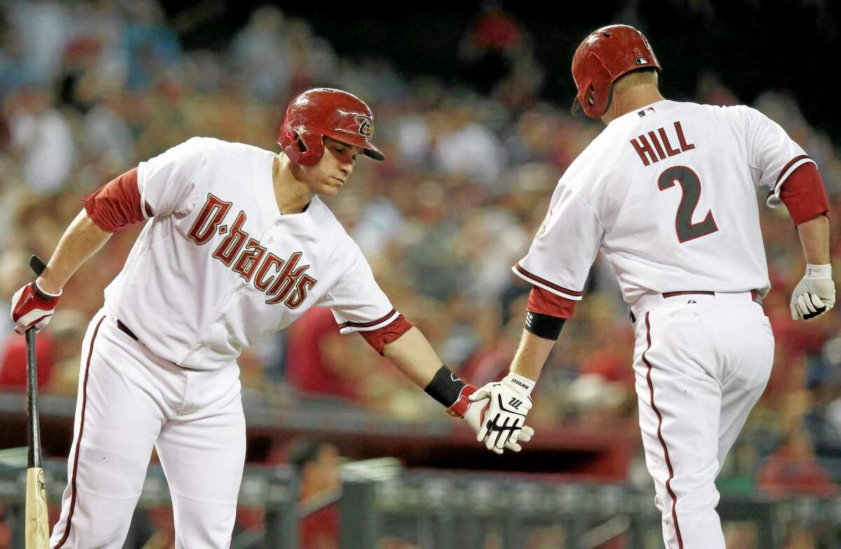 The Arizona Diamondbacks' Aaron Hill (2) celebrates his home run with teammate Miguel Montero, left, during a July 22 game in Phoenix.