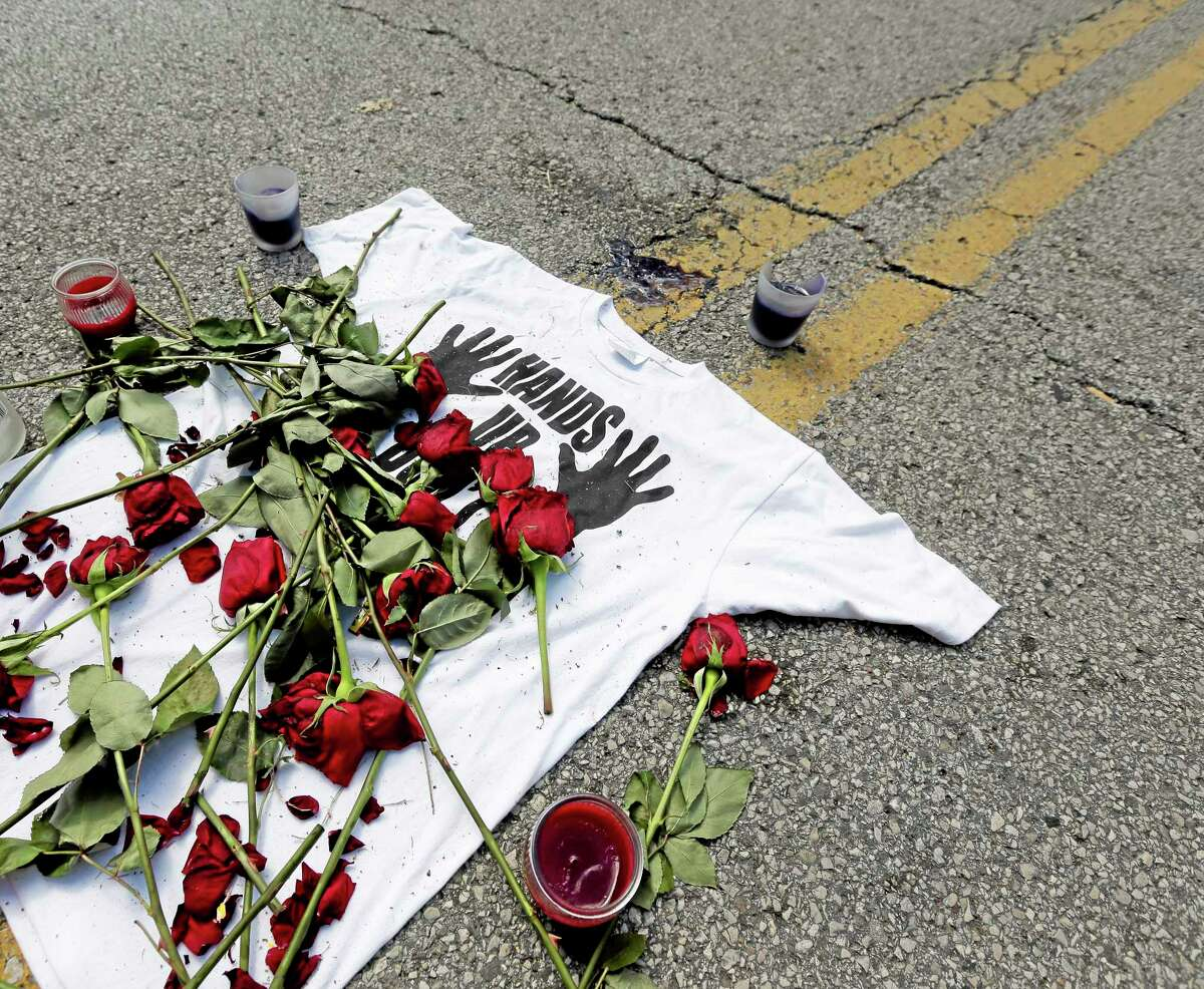 """A shirt reading """"hands up don't shoot"""" is covered with roses Tuesday, Aug. 19, 2014, at the spot Michael Brown was killed by police Aug. 9 in Ferguson, Mo. (AP Photo/Charlie Riedel)"""