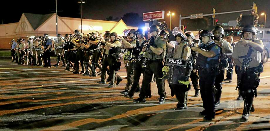 Police advance to clear people Monday, Aug. 18, 2014, during a protest for Michael Brown, who was killed by a police officer Aug. 9 in Ferguson, Mo. Brown's shooting has sparked more than a week of protests, riots and looting in the St. Louis suburb. (AP Photo/Charlie Riedel) Photo: AP / AP