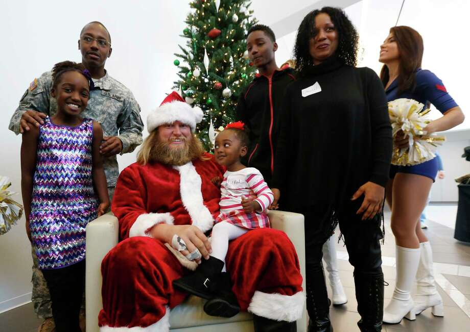 Lian Taylor, 2, of Bayonne, N.J., sits on the lap of New York Jets center Nick Mangold, posing as Santa Claus during the team's holiday party for military families on Friday in Florham Park, N.J. Photo: Julio Cortez — The Associated Press  / AP