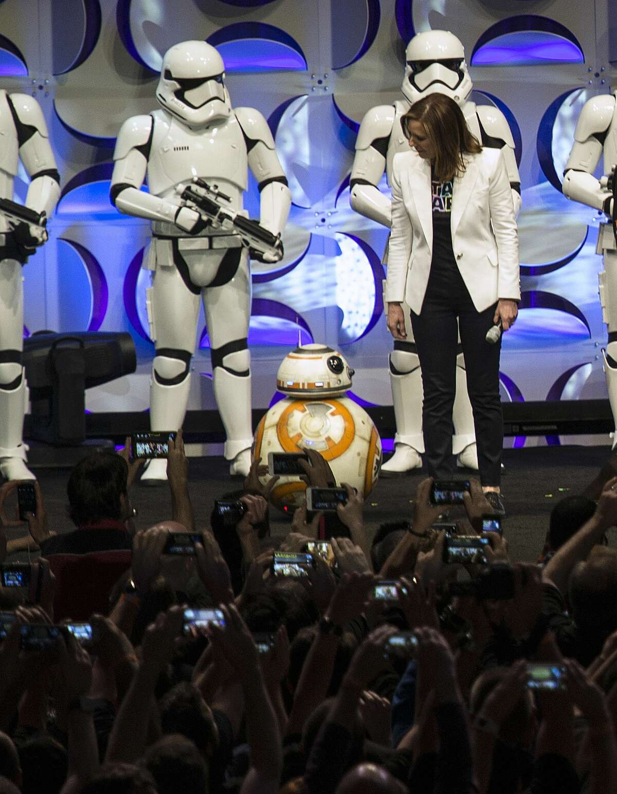 """Producer Kathleen Kennedy, right, looks down at the BB-8 droid, featured in the upcoming film, """"Star Wars: The Force Awakens,"""" during the Star Wars Celebration at the Anaheim Convention Center in Anaheim, Calif."""