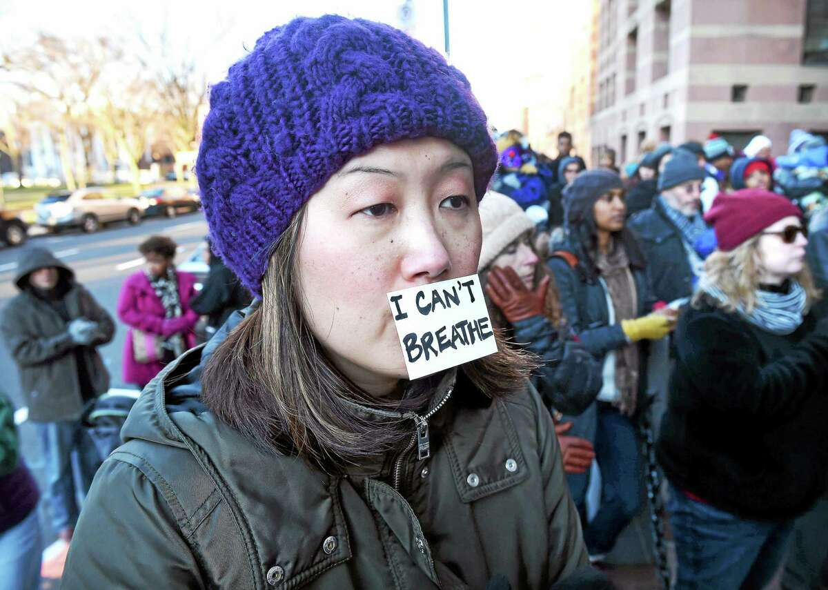 (Arnold Gold-New Haven Register) Emily Byrne (center) of New Haven listens to speakers at the Rally for Peace, Journey for Justice organized by the Greater New Haven NAACP, the Greater NAACP Youth Council and the Greater New Haven NAACP College Chapters in front of City Hall on 12/7/2014.