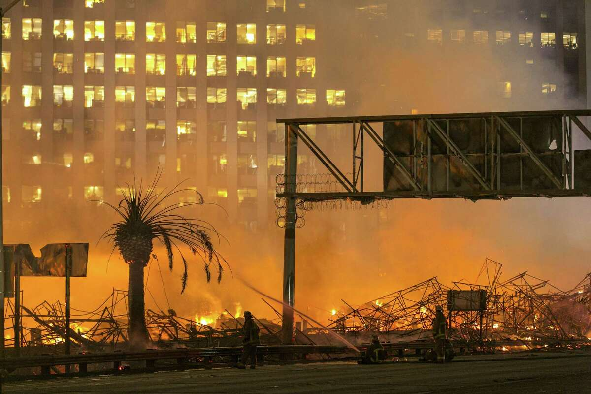 Los Angeles County firefighters battle a fire at an apartment building under construction next to the Harbor CA-110 Freeway in Los Angeles, early Monday, Dec. 8, 2014. The building was not occupied, the Los Angeles Fire Department reported.