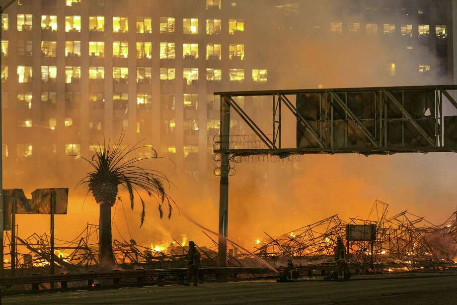 Los Angeles County firefighters battle a fire at an apartment building under construction next to the Harbor CA-110 Freeway in Los Angeles, early Monday, Dec. 8, 2014. The building was not occupied, the Los Angeles Fire Department reported. Photo: (AP Photo/Damian Dovarganes) / AP