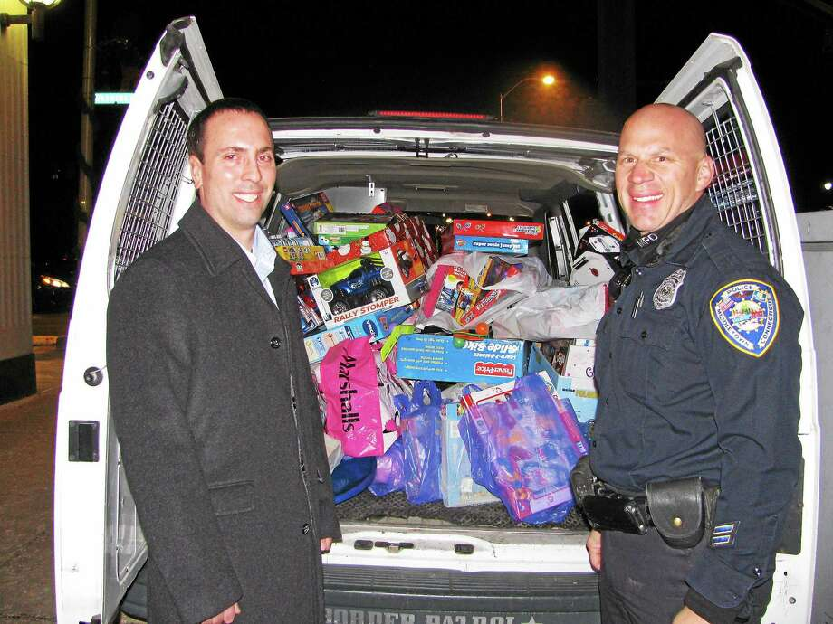 From left, Eric Kane of the Middlesex United Way Young Leaders Society and Middletown police officer Anthony Knapp show off Stuff-a-Cruiser donations in this archive photograph. The fifth annual Stuff-a-Cruiser Holiday Social & Toy Drive will be held Thursday at Esca. Photo: File