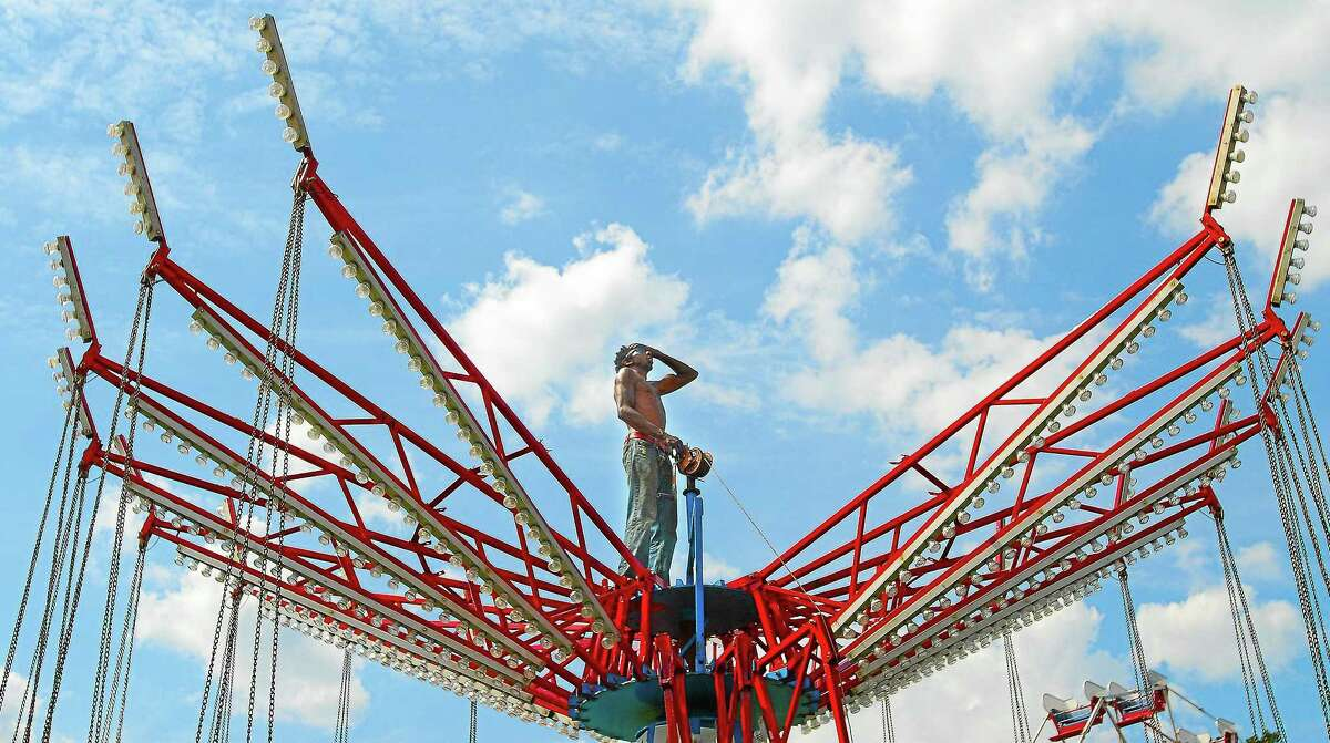 Meriden resident Steven Hubbard wipes the sweat from his brow in this 2012 file photo while setting up the Musical Chairs for the Riverport Festival at Pierson Park in Cromwell.